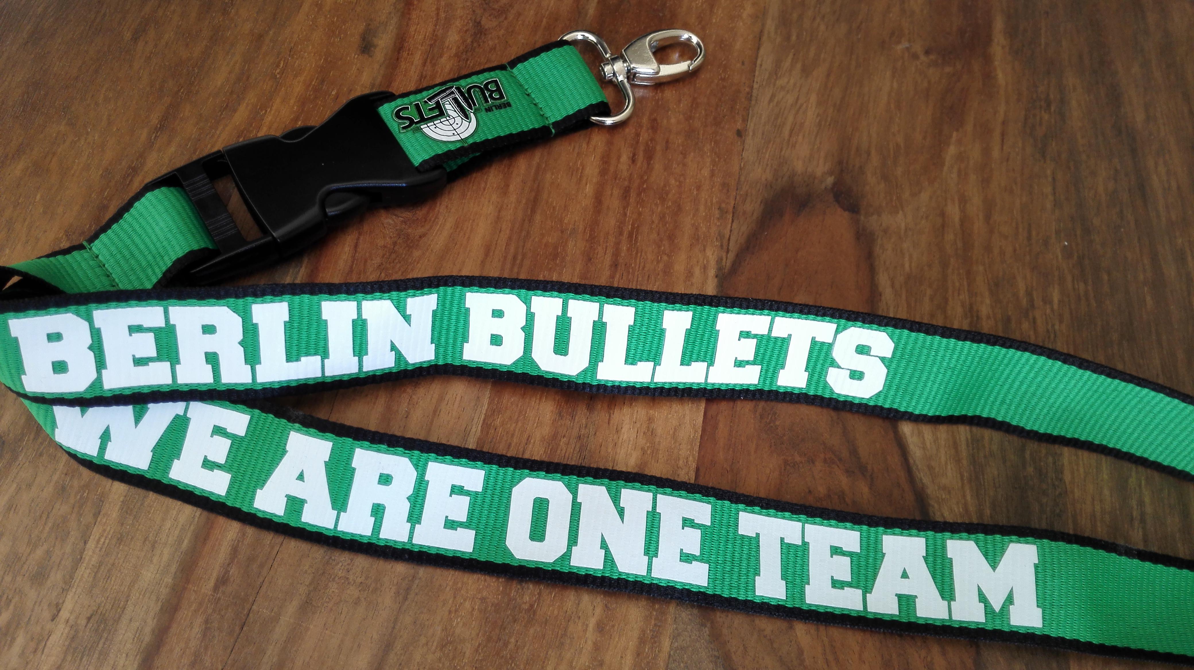 Foto zeigt ein Schlüsselband in grün und weiß mit dem Schriftzug We are one Team